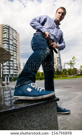 Handsome man showing new sneakers - stock photo
