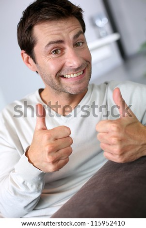 Handsome man showing thumbs up - stock photo