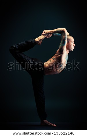 Handsome man shows different yoga exercises over black background.