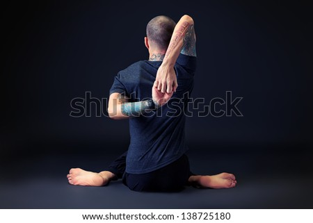 Handsome man shows different yoga exercises over black background. - stock photo