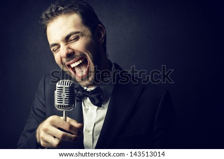 handsome man singing with microphone - stock photo