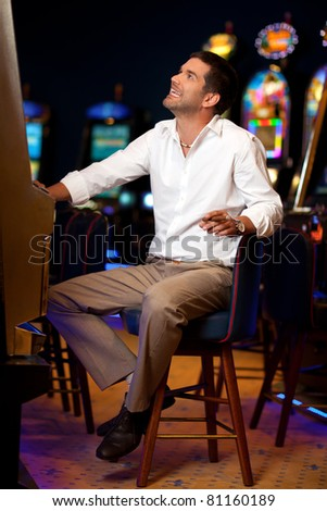 handsome man sitting by the slot machine, hoping to win