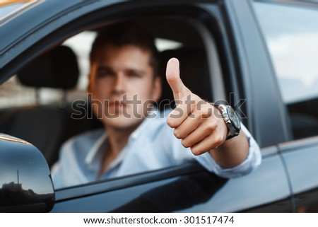 Handsome man sitting in a car and holding thumbs up