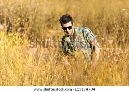 Handsome man sitting in a field - stock photo