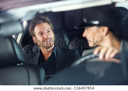 Handsome man sitting in luxury car, female chauffeur driving. - stock photo