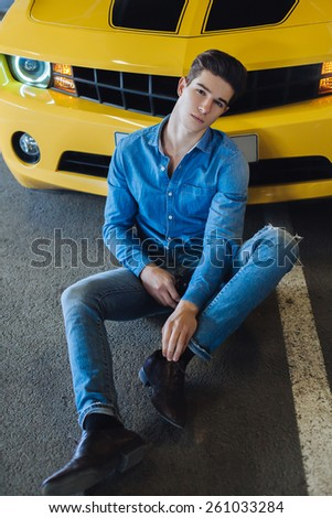 Handsome man sitting near the modern sport car - stock photo