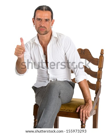 Handsome man sitting on a chair and showing ok sign on a white background