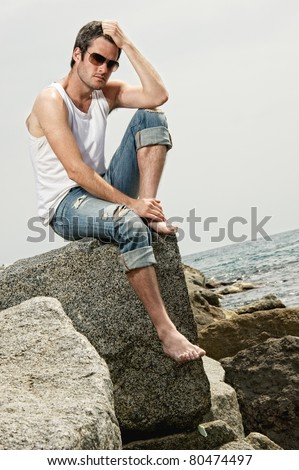 Handsome man sitting on a rock - stock photo