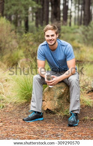 Handsome man sitting on a stone holding a water bottle in the nature