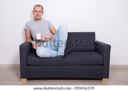 handsome man sitting on sofa and watching tv with cup of tea or coffee - stock photo
