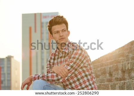 Handsome man sitting on stone stairs in summertime over city background - stock photo