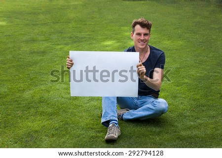 Handsome man sitting on the grass with white board - stock photo