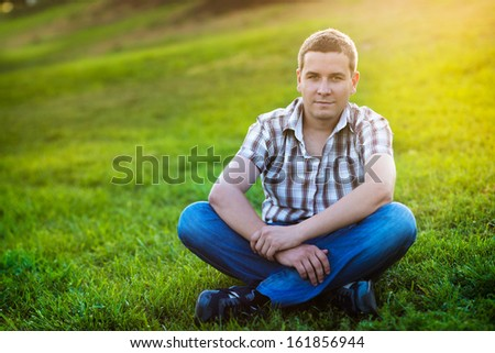 Handsome man sitting on the green grass in the park - stock photo