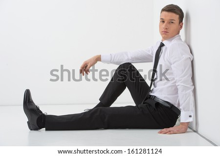 Handsome man sitting on the white floor. Wearing modern business suite