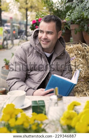 handsome man sitting outside in a cafe and reading a book