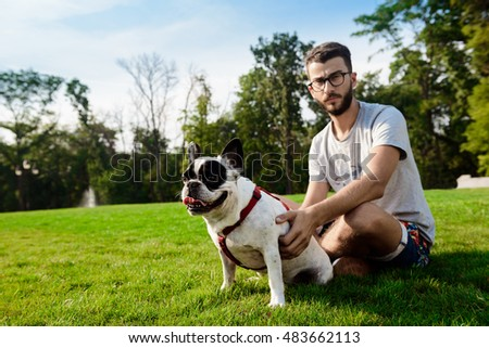 Handsome man sitting with french bulldog on grass in park.