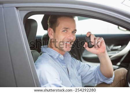 Handsome man smiling and holding key in his car - stock photo