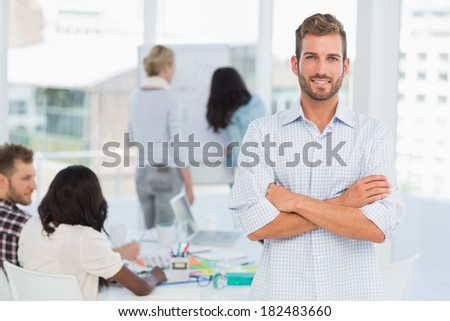 Handsome man smiling at camera while his colleagues are working in creative office - stock photo