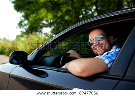Handsome man smiling in his own car