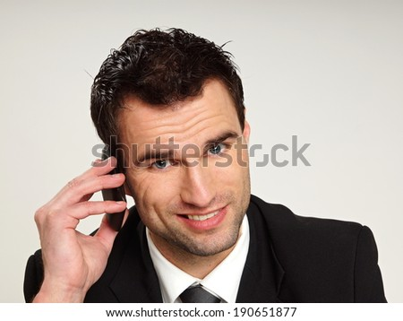 Handsome man smiling in suit talks at mobile phone