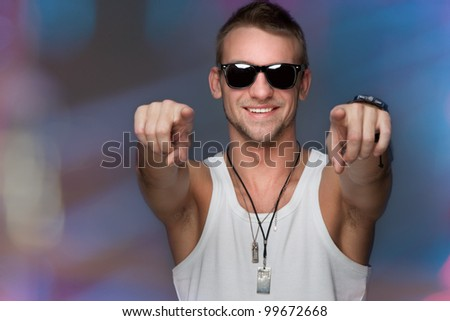 handsome man smiling into the camera and points - stock photo
