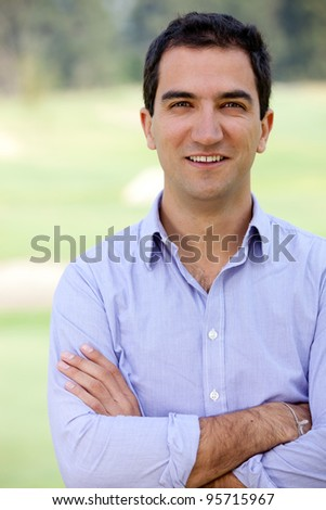 Handsome man smiling outdoors with arms crossed looking casual