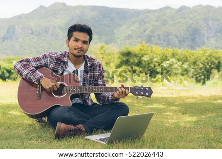 Handsome man smiling, playing guitar. Chord on laptop. Sitting on green grass. Nature background.