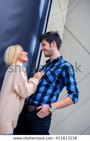 Handsome man smiling to a sexy blonde woman and looking at each other - stock photo