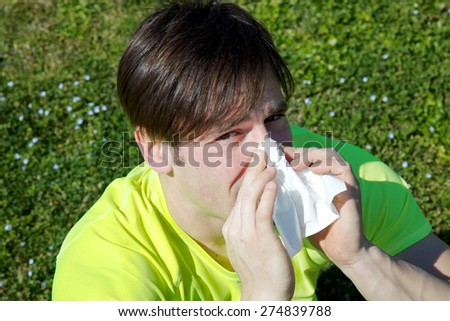 Handsome man sneezing in handkerchief - stock photo