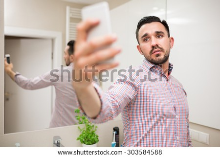 Handsome man standing in bathroom and using cologne water