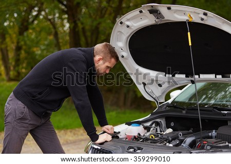 Handsome man standing in front of a broken car - stock photo