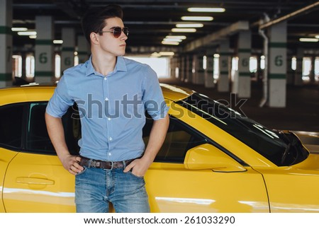 Handsome man standing near the modern sport car - stock photo