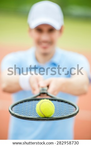 Handsome man stood in front of tennis court holding racket. Sport outdoors. - stock photo