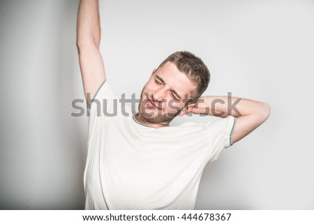 handsome man stretching after sleep, isolated on a gray background