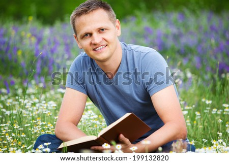 Handsome man studying outdoors with a book.