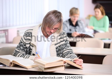 Handsome man studying while sitting at desk with lot of books - stock photo