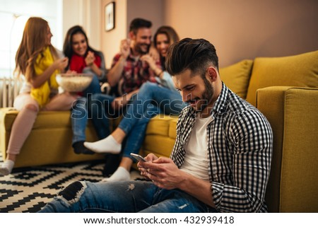 Handsome man surfing the internet on a home party.