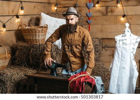 Handsome man tailor or dressmaker with beard and moustache in hat poses near vintage sewing machine in rustic workshop