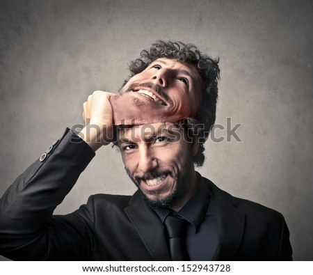 handsome man takes off his mask - stock photo