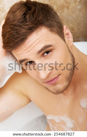 Handsome man taking a bath and enjoying it.
