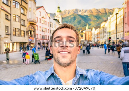 Handsome man taking a selfie photo in Innsbruck at Maria Theresa square. Joyful traveler take souvenir photo during journey in old mountain town. Adventure travel lifestyle concept around world trip. - stock photo