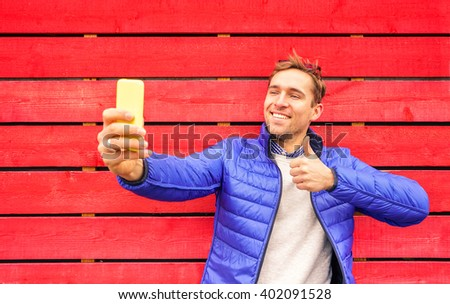 Handsome man taking selfie against red wooden wall in London square. Travel adventure lifestyle around word destination. Multicolored photo with young guy making thumbs up for sending pic to friends. - stock photo