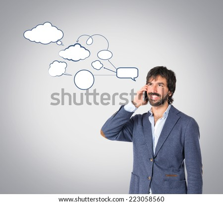 Handsome man talking to mobile over grey background - stock photo