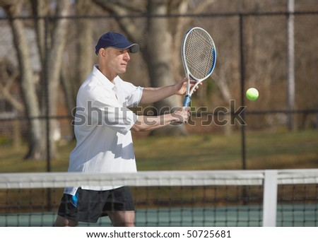 Handsome man tennis player at court hitting ball - stock photo