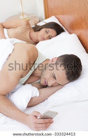 Handsome man texting on the cell phone while laying in the bed with his girlfriend