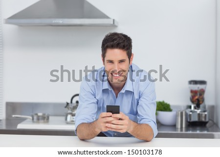 Handsome man typing on his smartphone in kitchen - stock photo