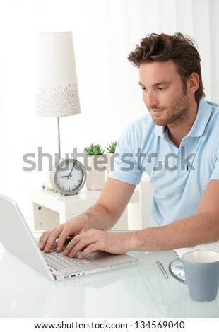 Handsome man typing on laptop computer keyboard, looking at screen, smiling. - stock photo