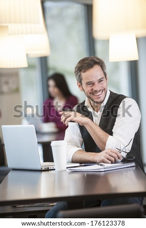 handsome man using a laptop in a cafe - stock photo