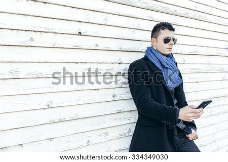 Handsome man using his smart phone on white wooden background with blank space,selective focus - stock photo