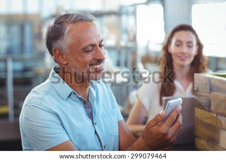 Handsome man using his smartphone in the bakery store - stock photo